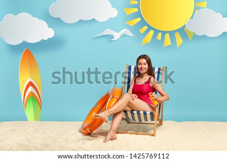 Restful glad woman applies sunblock cream on leg, poses at beach in chair, has active summer rest, surfboard and lifebuoy near, blue background with yellow sun and little clouds. Hot day at sea #1425769112