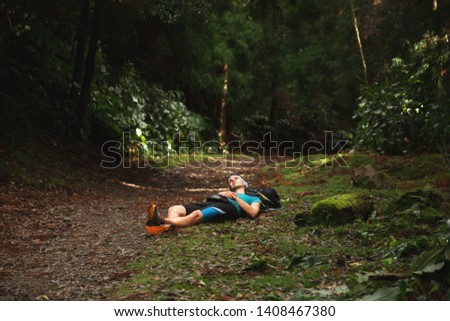 Restful young man lying down on ground in forest. Sao Miguel island, Azores #1408467380