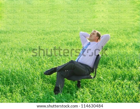 Resting businessman relaxing on a chair on a green meadow