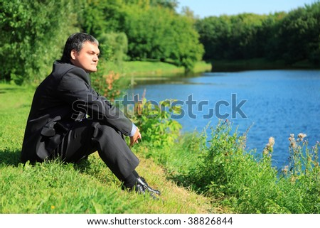 resting businessman sitting on river bank