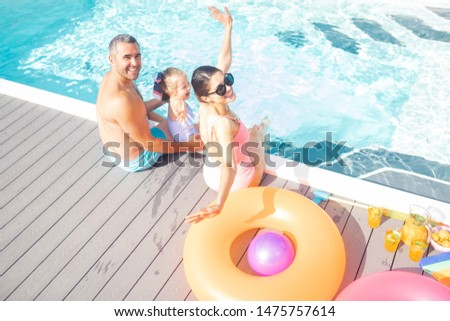 Resting near pool. Happy parents and lovely daughter feeling cheerful resting near pool #1475757614