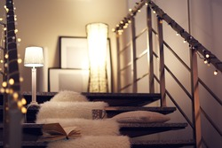 Resting-place with electric garland, cup of tea, book and lamps on modern stairs
