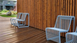 Resting point inside residential area courtyard in rainy day.Two wet metal chairs with raindrops of modern design close-up on a background of wet wooden shield.Comfortable urban public furniture.