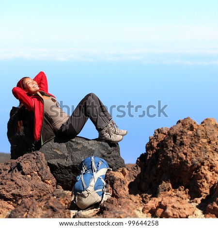 Resting relaxing woman hiker lying down enjoying the sun during hiking travel trek on volcano Teide, Tenerife, Canary Islands, Spain. Beautiful young female hiker.