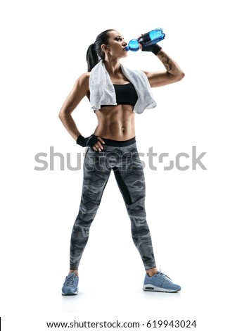 Resting time. Sporty girl with towel on shoulders drink water. Photo of muscular fitness model isolated on white background. Health concept.