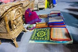 Resting woman seller displaying woolen carpets , door mats, handicraft products. At hastashilpomela or handicrafts fair at Kolkata, West Bengal, India.
