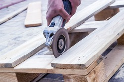 Restore old wooden planks with angle grinder. Close up of a carpenter and small buiness owner working in woodwork workshop, Process with angle grinder. Carpenter work with wooden. Side view.