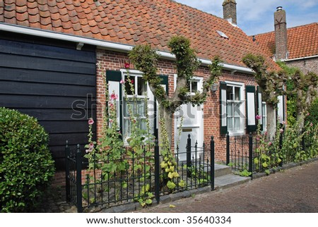 Restored little historic farmers house with shutters, black tar weatherboarding and traditional garden with pollard trees in the touristic dutch city Veere