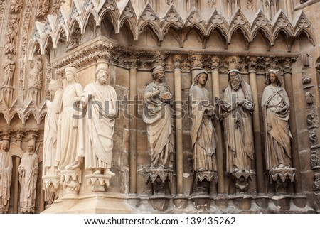 restored statues in contrast with the old ones, on the front of Cathedral of Notre-Dame, Reims, France