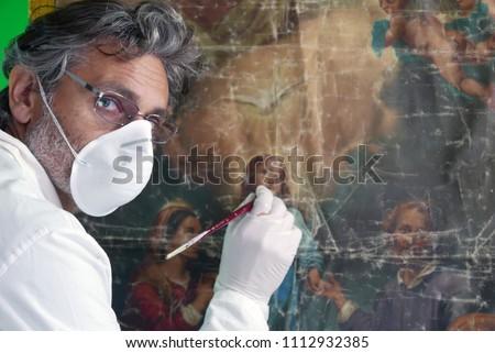 restorer working on oil painting , art restoration concept