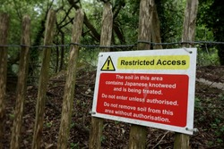 Restricted access warning sign. Focus on sign, one side of frame. The soil in this area contain Japanese Knotweed being treated. Do not enter unless authorised Do not remove soil without authorisation