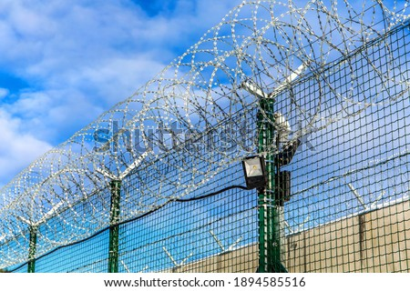 Restricted area - fence with barbed wire. Razor wire jail fence. Barrier border. Boundary security wall. Prison for arrest criminals or terrorists. Military zone
