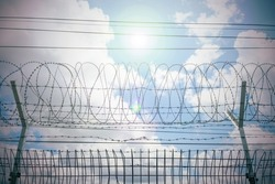 Restricted area with sky and sun, barbed bottom view and morning sun, Barbed wire fence and wire mesh with sky, Fence with barbed wire against the blue sky. Barbed wire barrier in restricted area.