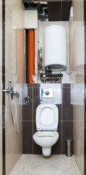 restroom repair. Restroom with removed tiles due to need to replace the riser and pipes. complex piping system, wall hung frame, plumbing manifold, boiler, riser,hygienic shower, riser, pipes