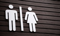 Restroom sign on a toilet door,on wood background.Toilet sign - Restroom Concept - black tone.WC / Toilet icons set. Men and women WC signs for restroom.