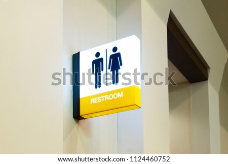 Restroom sign or toilet sign made of electric light box with man and woman icon set  symbol on white concrete wall background, modern, hygiene and clean restroom concept #1124460752