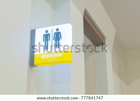 Restroom sign or toilet sign made of electric light box with man and woman icon set  symbol on white concrete wall background, modern, hygiene and clean restroom concept #777841747
