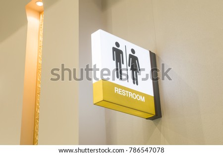 Restroom sign or toilet sign made of electric light box with man and woman icon set  symbol on white concrete wall background, modern, hygiene and clean restroom concept #786547078