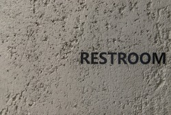 Restroom : signage in black letters. Characters on the bare cement wall background. Toilet sign, Restroom Concept, WC signs for restroom. No focus, specifically.