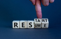 Resume and restart symbol. Businessman hand turns cubes and changes the word 'resume' to 'restart'. Beautiful grey background. Business and resume - restart concept. Copy space.
