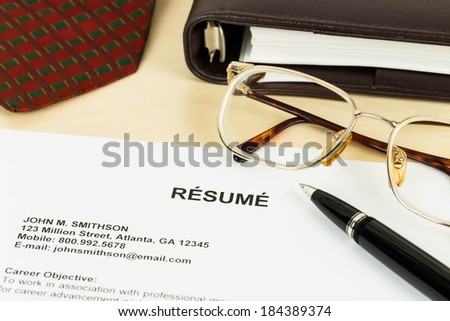 Resume, pen, neck tie, glasses, and notebook