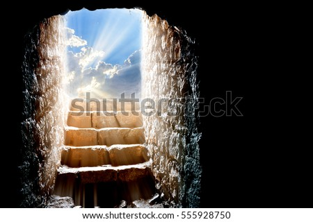 Resurrection of Jesus Christ. Religious Easter background, with strong light rays shining through the entrance into the empty stone tomb. Artistic strong vignette, contrast, dramatic dark-light edit. #555928750