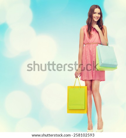 retail and sale concept - smiling woman in dress and high heels with many shopping bags