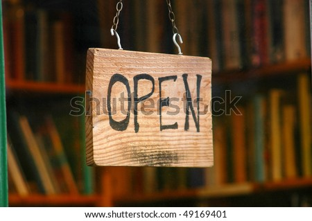 Retail and shopping image of an open sign in a book store window