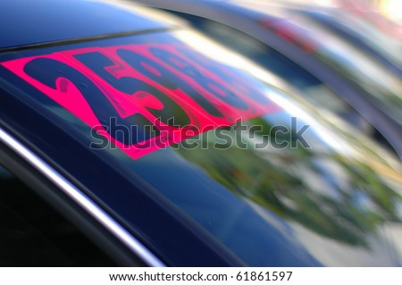Retail Business Image of Price Stickers on a Row of Used Cars, With Shallow Depth of Focus