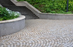 retaining wall at the large staircase in the park the flowerbed area is planted with rich greenery of perennials granite paving of cubes