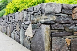 Retaining Wall Detail. Closeup of dry stone wall built with natural flagstones and wallstones of irregular shapes and sizes