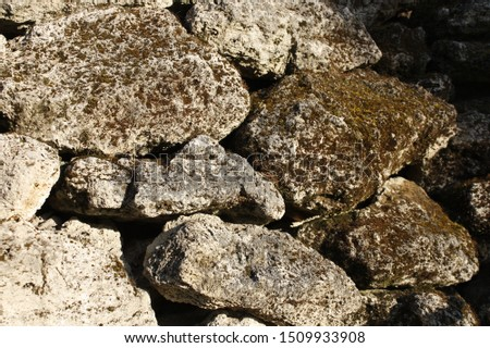 Retaining wall made of large stones. Large stones covered with moss close-up.