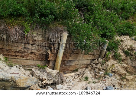 Retaining wall that has shifted allowing mud to flow around the wall of a steep slope.