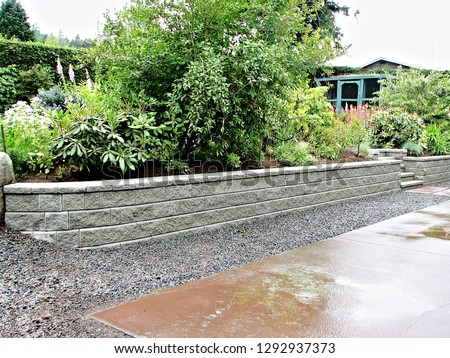 Retaining wall with stone blocks used as a source of material part of a garden landscape design offering a viable long term solution in any backyard project for any residential home owner