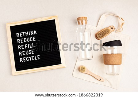 Rethink, reduce, refill, reuse, recycle. Black letter box with eco friendly shopping bag, bottle, coffee cup and brushes on white background. Zero waste sustainable lifestyle. Plastic free concept.  Foto stock ©