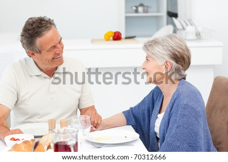 Retired couple eating  in the kitchen - stock photo