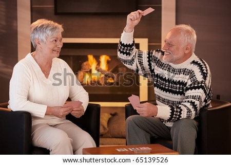 Retired couple playing cards in front of fireplace in living room at home, smiling.?