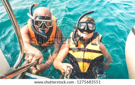 Retired couple taking happy selfie in tropical sea excursion with life vests and snorkel masks - Boat trip snorkeling in exotic scenarios on active elderly and senior travel concept around world #1275683551
