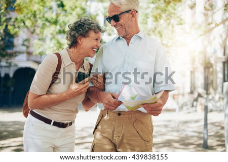 Retired couple walking around the town with a map. Smiling mature man and woman roaming around the city.