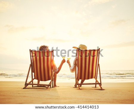 Retired couple watching the sunset enjoying a glass of wine