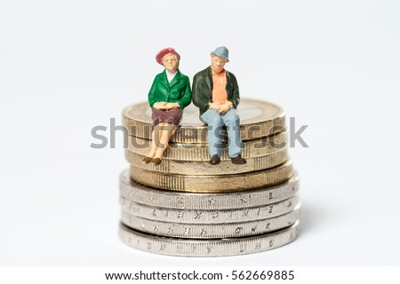 Retired / elderly couple sitting on euro coins #562669885
