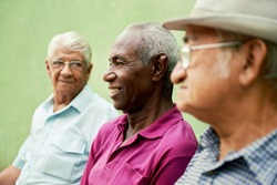 retired elderly people and free time, group of happy senior african american and caucasian male friends talking and sitting on bench in park