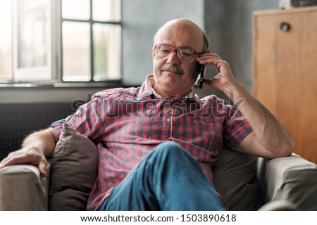 Retired hispanic man talking on phone sitting at living room. Discuss important questions.