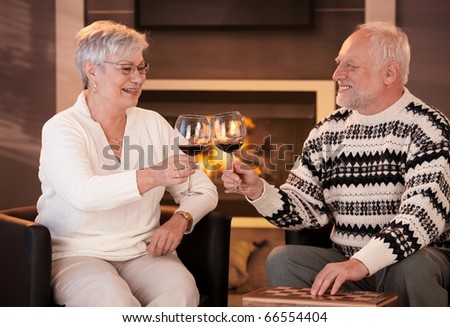 Retired husband and wife drinking red wine together in cosy living room, in front of fireplace, looking happy, smiling.?