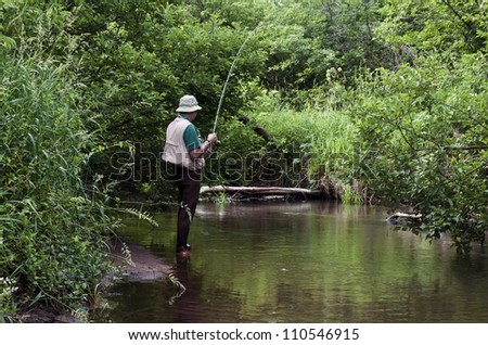 retired man fishing a small stream with a fly rod