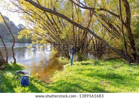 Retired man on holiday fly fishing for trout in Australia in beautiful environment