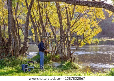 Retired man on holiday fly fishing for trout in beautiful countryside