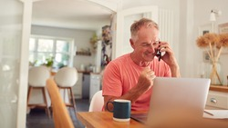 Retired Man On Phone At Home In Kitchen Using Laptop Celebrating Good News Or Winning