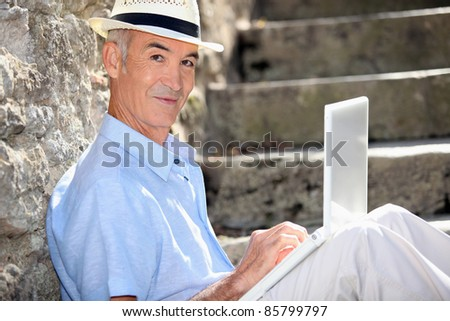 Retired man sat against stone wall with laptop