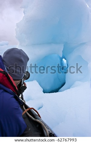 retired man traveling and taking picture of icebergs, greenland